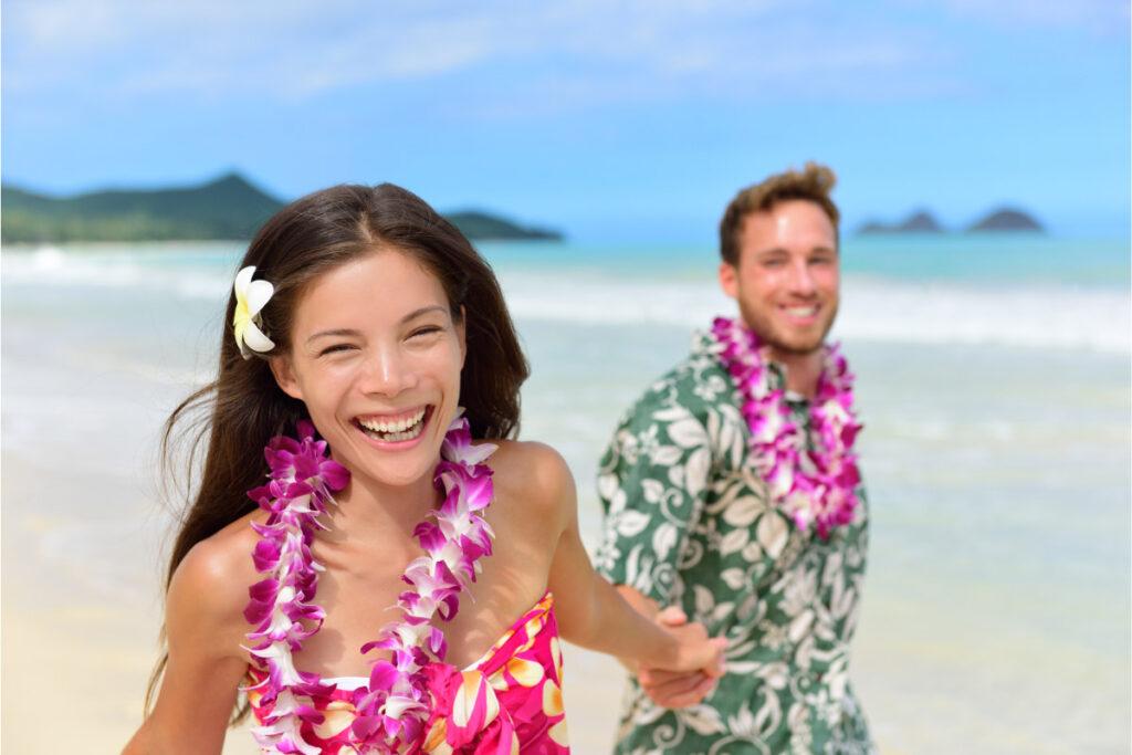 couple on beach wearing leis