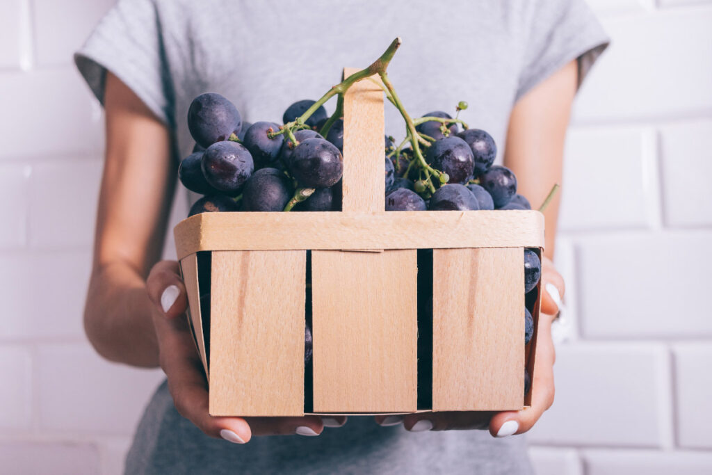 woman holds wooden basket of grapes
